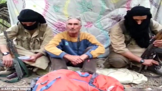 French tourist, Herve Pierre Gourdel sitting between two armed jihadists at an undisclosed location