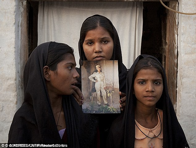 The daughters of Mrs Bibi pose with an image of their mother who faces death by hanging