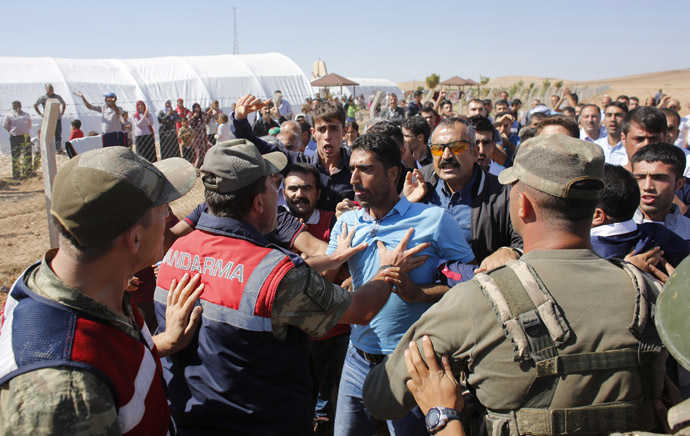 Turkish soldiers try to prevent Turkish Kurdish protesters to march to the Mursitpinar border crossing on the Turkish-Syrian border