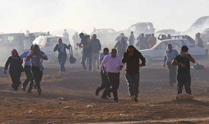 Turkish Kurdish protesters run from tear gas fired by Turkish soldiers near the Mursitpinar border crossing on the Turkish-Syrian border