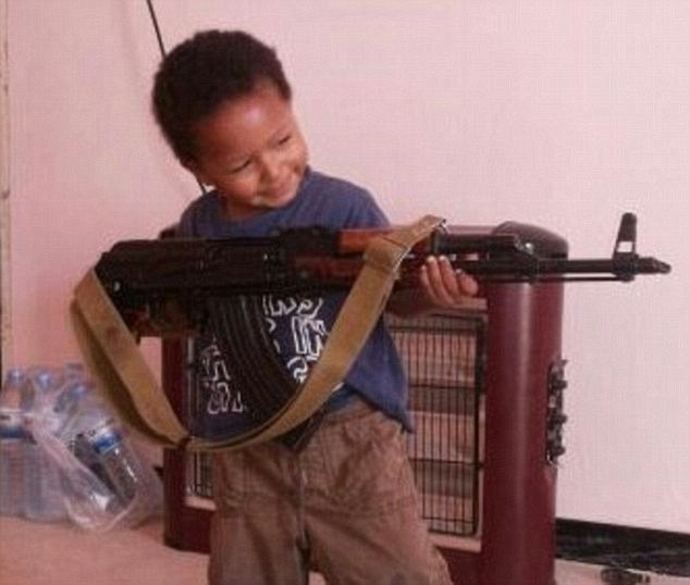Khadijah Dare's young son poses with an AK-47rifle.  This is a s