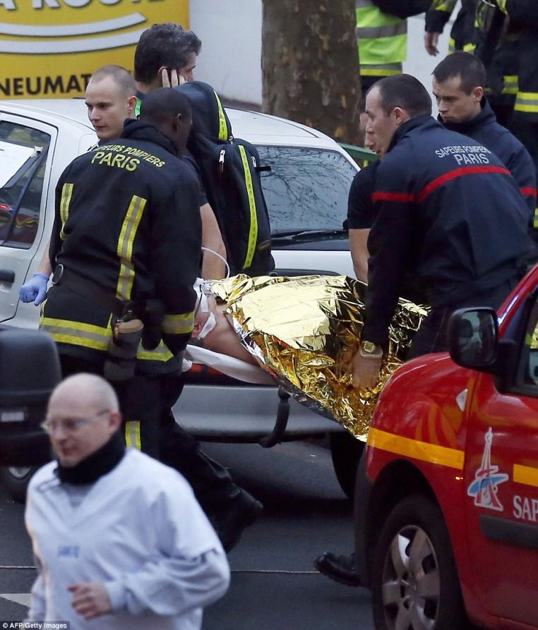 Trabajadores de los servicios de rescate evacuan persona lesionada en una camilla después del tiroteo en Montrouge que dejó un muerto mujer policía