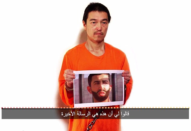 Japanese hostage Kenji Goto holding photos of Jordanian pilot also threatened with beheading by the Islamic State