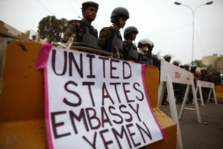 Riot policemen stand guard during a protest to demand the release of Yemeni detainees in the prison of Guantanamo Bay, outside the U.S. embassy in Sanaa