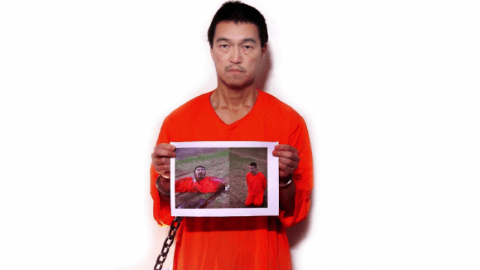 Kenji Goto sosteniendo una foto de una Haruna Yukawa decapitado