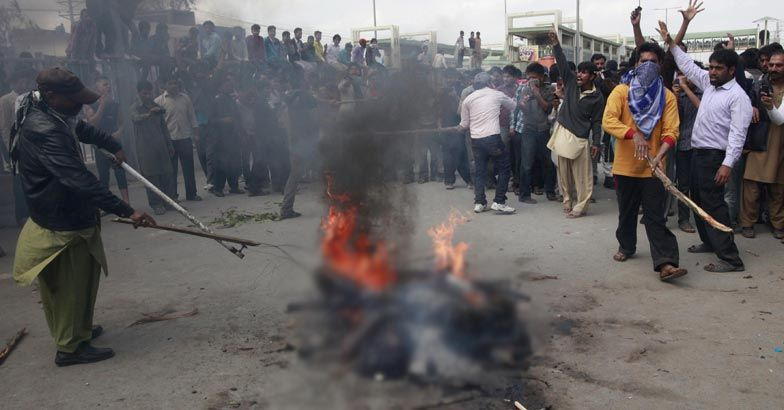 Enraged Christians burn a man they suspected of being involved in bomb attacks on churches, after lynching them in Lahore