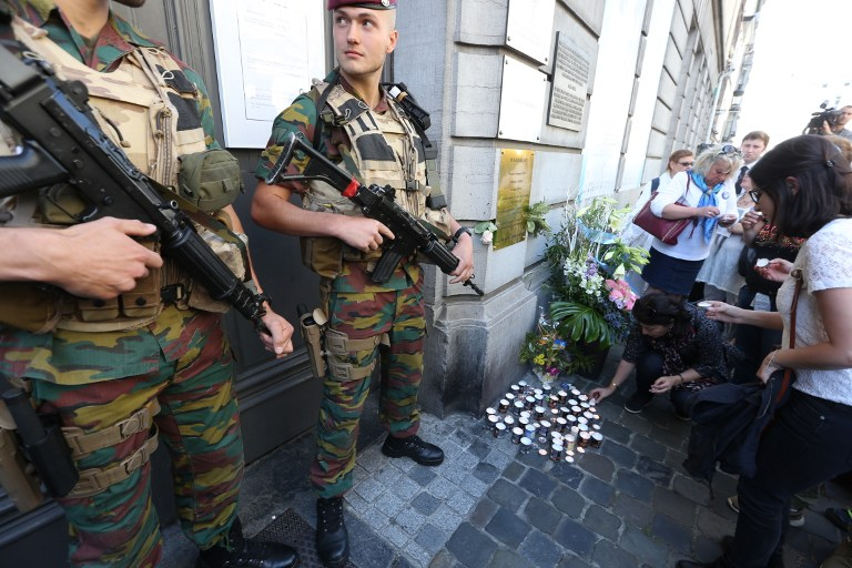 People lay down candles as soldiers stand guard at the entrance of the Jewish museum in Brussels, on 24, May 2015, a year after a gunman murdered four Jews at the museum.