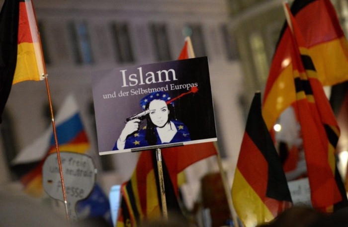 "Members of the anti-Islamic Pegida alliance gather and hold up a sign that reads ""Islam and Europe's suicide,"""