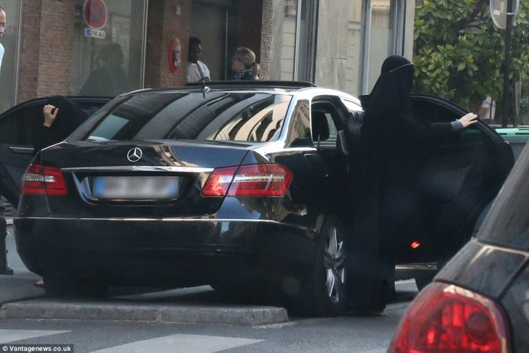 Gisele and her sister emerge at the clinic in Paris, both wearing burqas