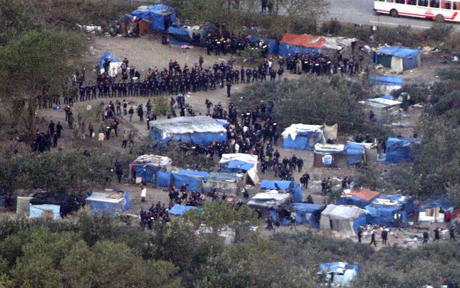 """Los agentes de policía rodean el campamento de ilegales improvisada conocida como la """"selva"""" en Calais"""