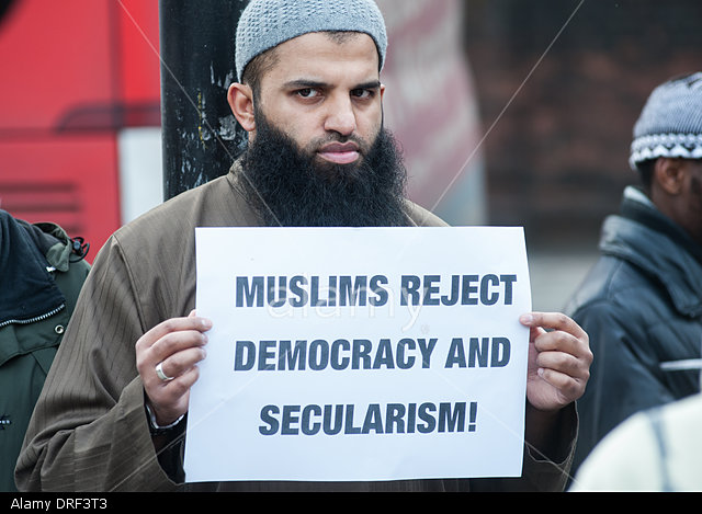 """London, UK. 24th January 2014. Abu Walaa, founder of Muslim Prisoners,holds a placard reading """"Muslims reject democracy and secularism!"""" outside the Regents Park Mosque. © Piero Cruciatti/Alamy Live News"""
