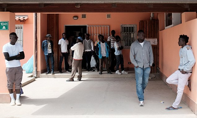 Migrants stand at the Cara Mineo Villas, a hosting centre for asylum
