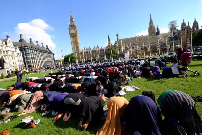 Muslims lifting their assess to allah in front of the Parliament