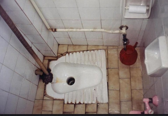 [An Islamic Squatting Style Toilet, with Water Jug]