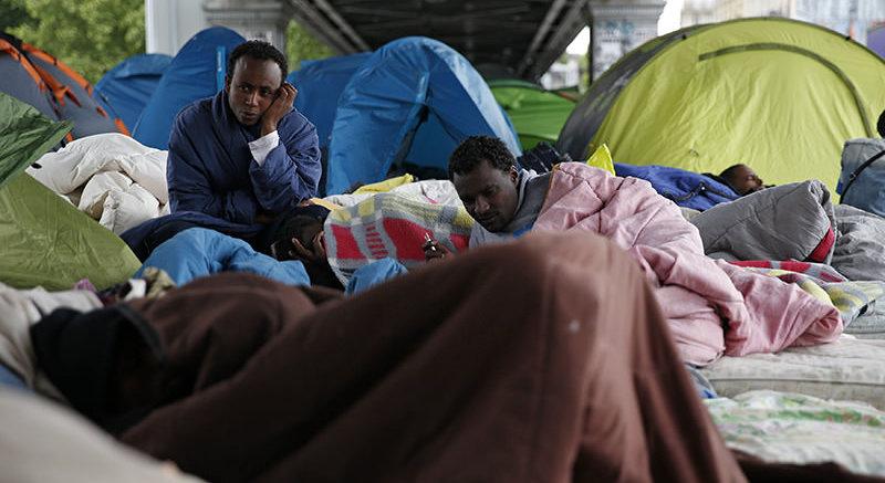 Los inmigrantes de Eritrea se sientan cerca de tiendas de campaña, ya que viven en un campamento improvisado debajo de un puente de metro en París