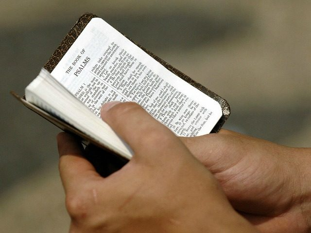 Un adorador-sostiene-un-pequeño-Biblia-640x480