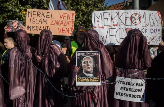 Protesters wearing a burkha hold banners during a demonstration against German Chancellor Angela Merkel on August 25, 2016 in Prague