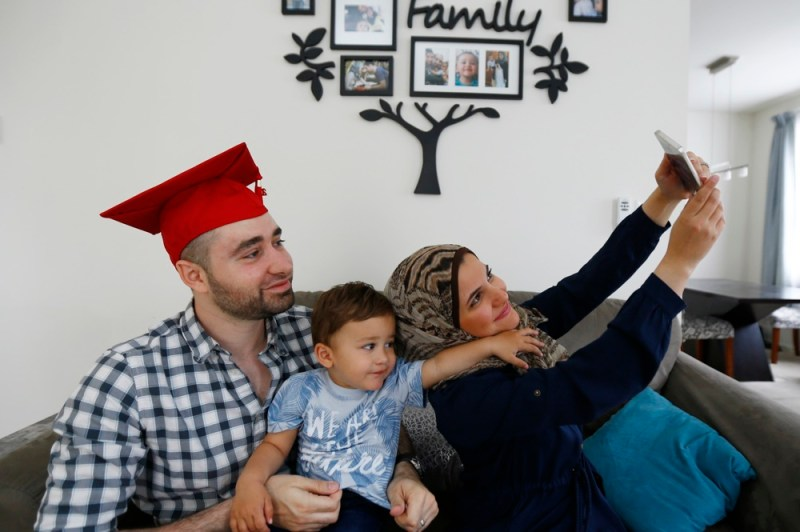"In a photo taken Saturday, May 21, 2016, Mohamad Bassel Khair, left, holds his son, Sami Kahir, 2, as his wife Lama Alassil takes a photo of them to post on the Snapchat application during a photo session with The Associated Press in his home in Clifton, N.J. Khair, of Damascus, Syria, is graduating from New Jersey's Montclair State University with a master's in nutrition and food science and is now seeking asylum in the U.S. for his family. ""They gave me a full scholarship, including rooming,"" Khair said. ""They were so helpful for me."" (AP Photo/Julio Cortez)"