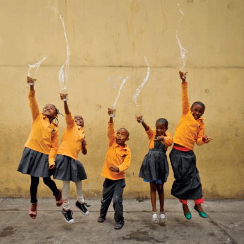 Cinco niños etíopes visten camisas amarillas y faldas y pantalones largos de color verde como parte de sus uniformes escolares.  Lanzan vasos de agua al aire de forma artística, mirando hacia arriba y sonriendo.