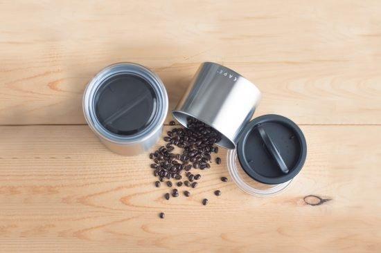 Una toma aérea del producto de tres latas de Airscape, una de las cuales tiene un juego de granos de café derramados.
