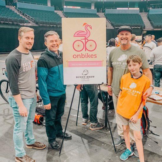 Un grupo de personas sonríe en un estadio frente a un cartel de Onbikes en un evento de construcción de bicicletas.