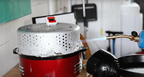 Un soplete arroja llamas sobre una olla arrocera con una canasta superior de vapor envuelta en papel de aluminio.