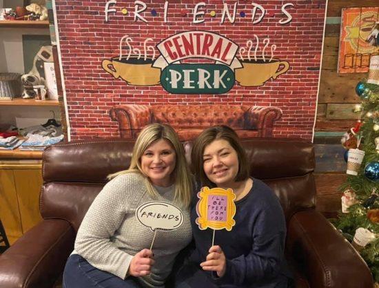 Dos personas, una rubia y una morena, se paran sonriendo frente a un letrero que hace referencia a la tienda central de beneficios de amigos.