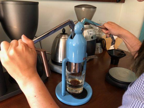 Dos manos presionando las palancas del cafelat.