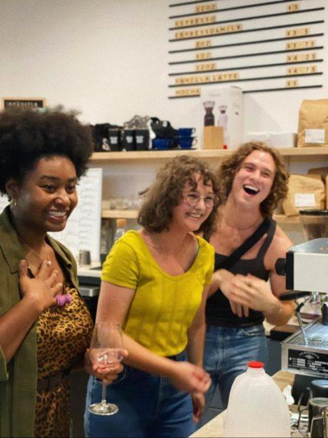 Tres personas están juntas sonriendo y mirando a un grupo que no está en la imagen.  Están frente a una máquina de café espresso.