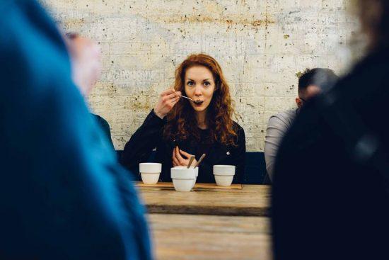 Una mujer pelirroja se sienta en una mesa con una cuchara en la boca.  Hay tres tazones de fuente blancos frente a ella.