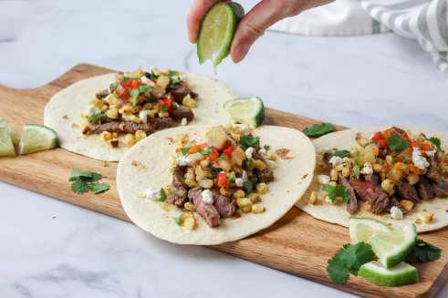 grilled steak and elote tacos with lime being squeezed on top.