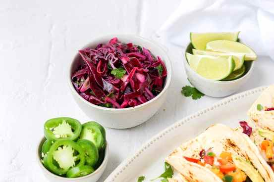 bowl of fresh cabbage slaw with jalapenos and lime wedges