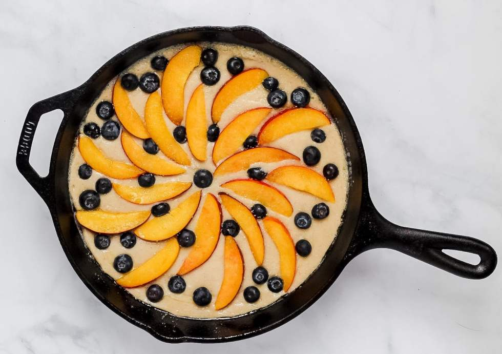 peach blueberry cobbler in cast iron pan before baking