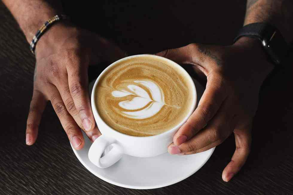 hands holding a latte with simple latte art