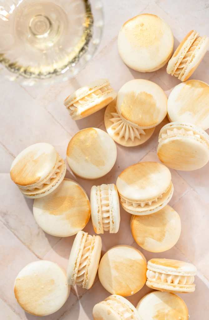 champagne macarons with gold paint and glass of champagne