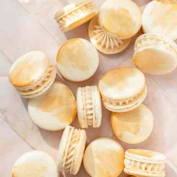 close up shot of champagne macarons with gold paint