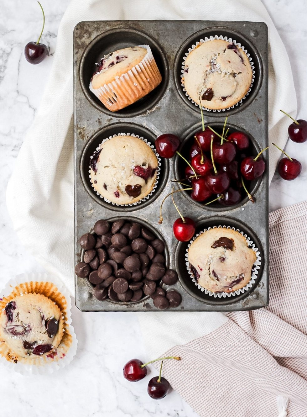 Chocolate cherry muffins in muffin tin with extra cherries and chocolate chips