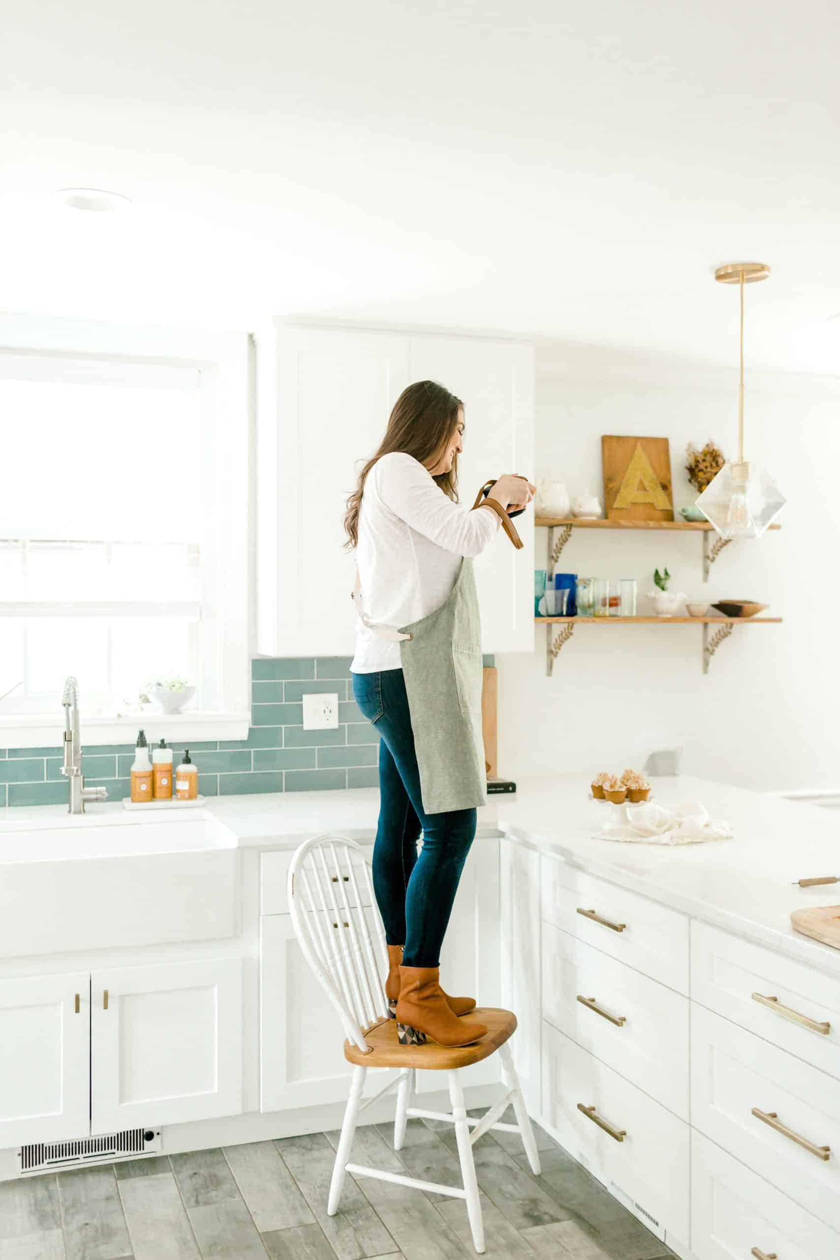 A person standing on chair in a kitchen