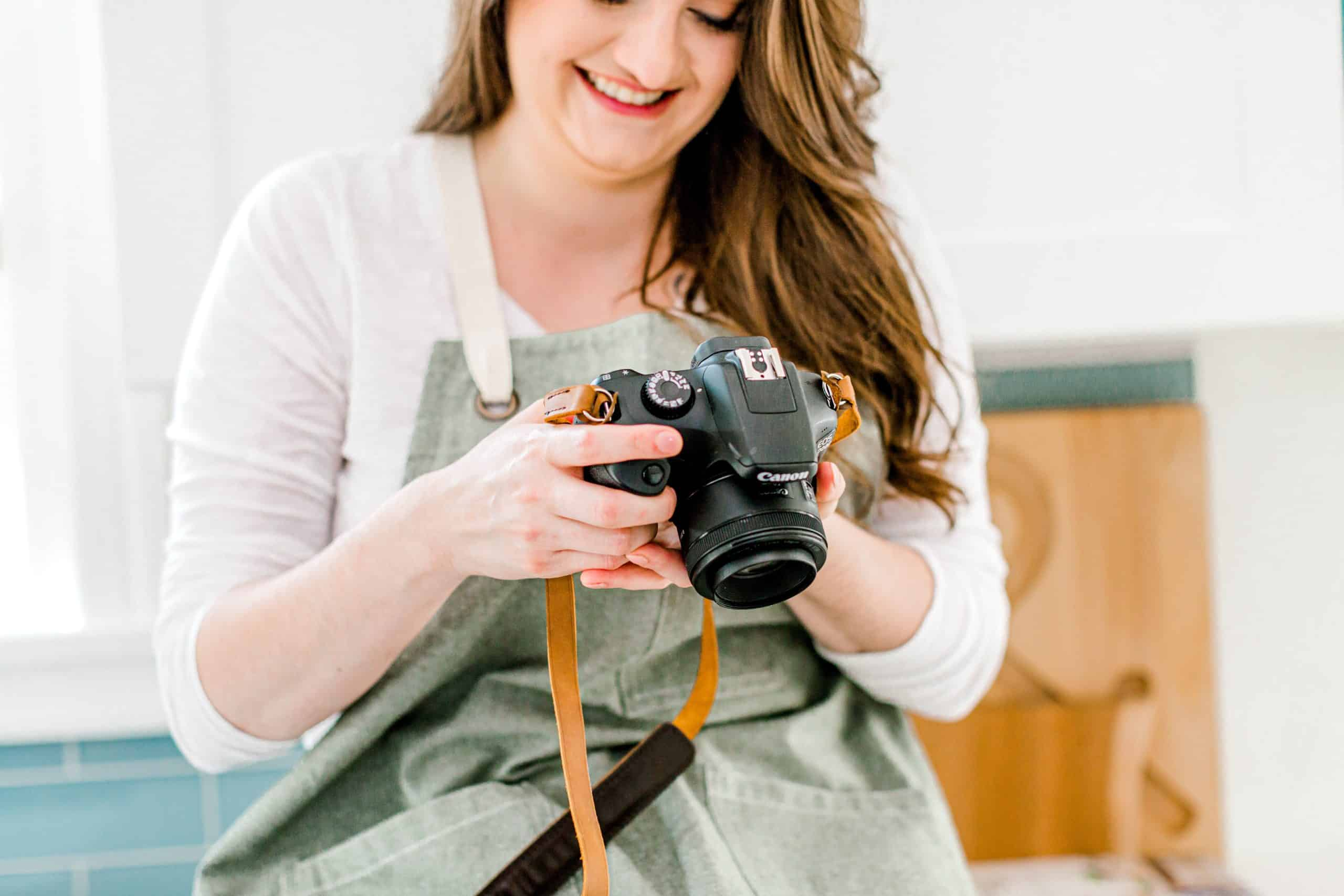 A person holding a camera and smiling
