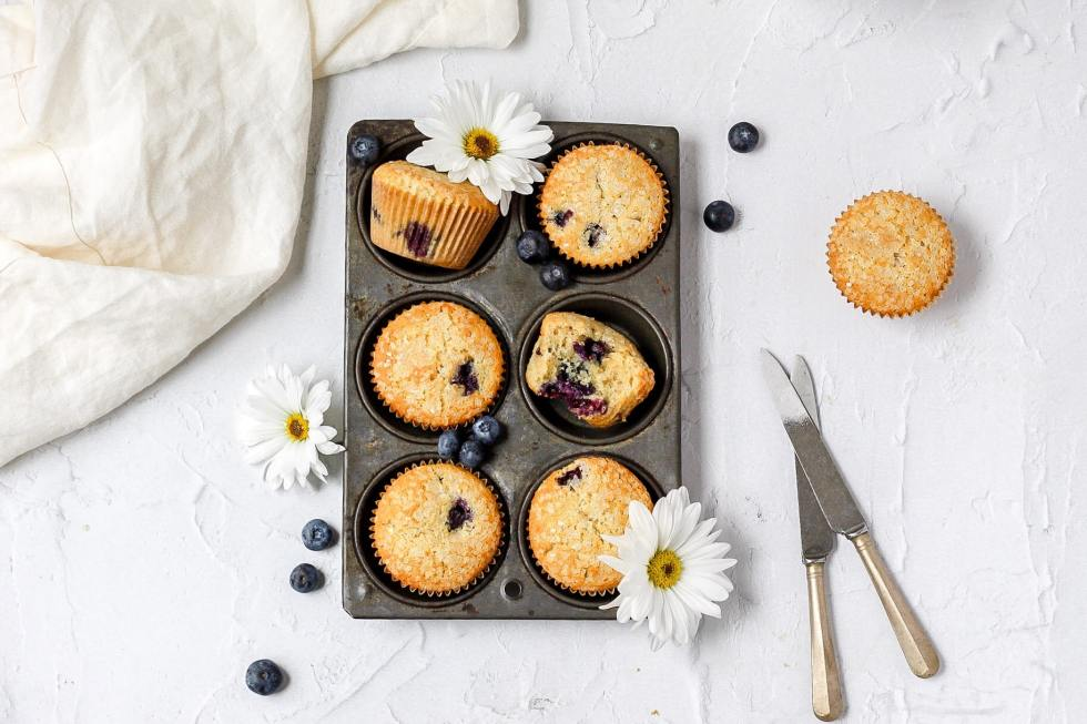 brown butter blueberry muffins in a rustic muffin tin