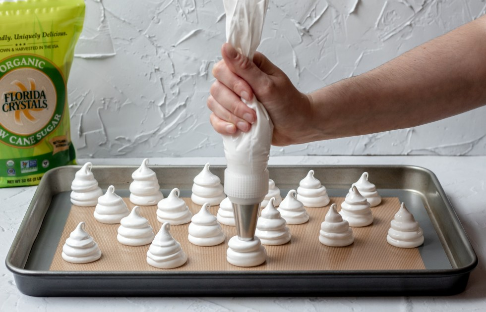 action shot of piping ghost meringue cookies