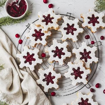 cranberry linzer cookies shaped like snowflakes