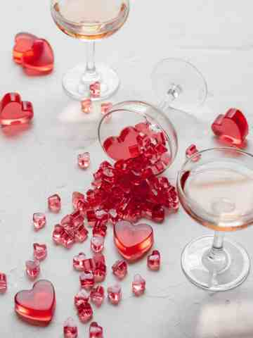 heart shaped rose gummies spilling out of wine glass