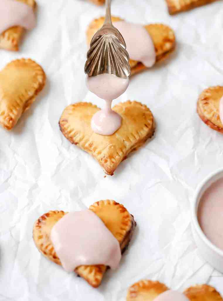 heart hand pies with strawberry filling and icing drizzle