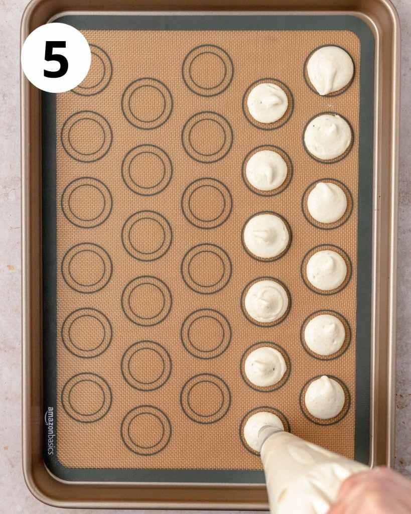 piping macarons onto baking sheet