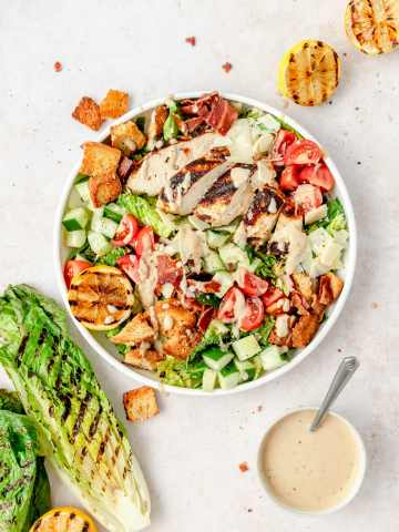 grilled chicken caesar salad in bowl with grilled romaine
