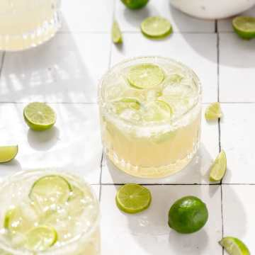 close up shot of key lime margaritas with slices of key limes