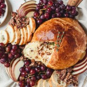 close up shot of baked brie with honey and pecans