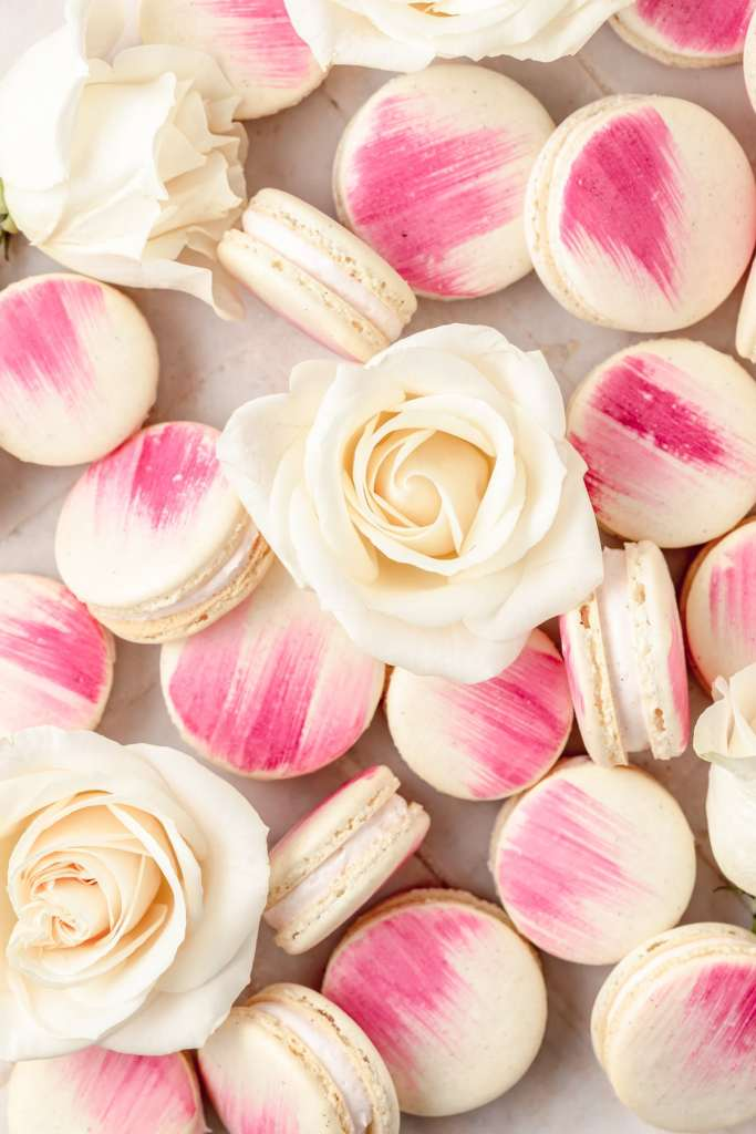 vanilla bean rose macarons with pink streaks and white roses