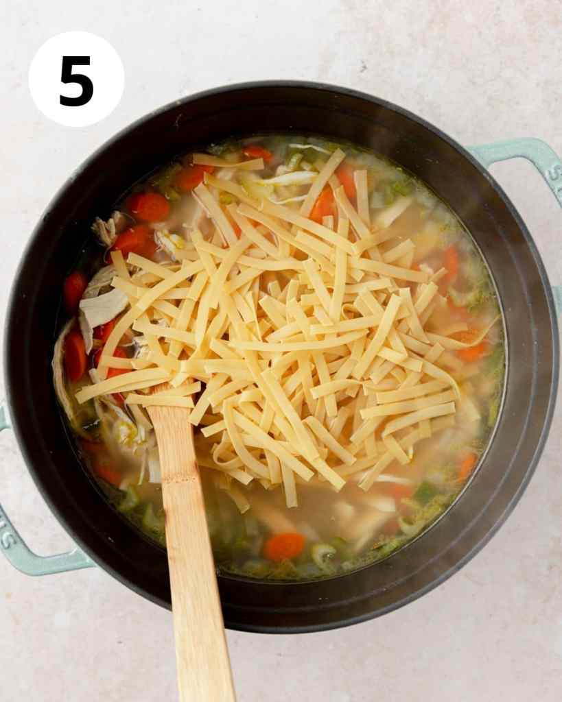 adding egg noodles to chicken soup